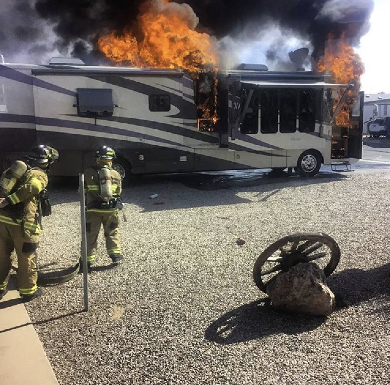 firefighters running a hose to an RV that is on fire