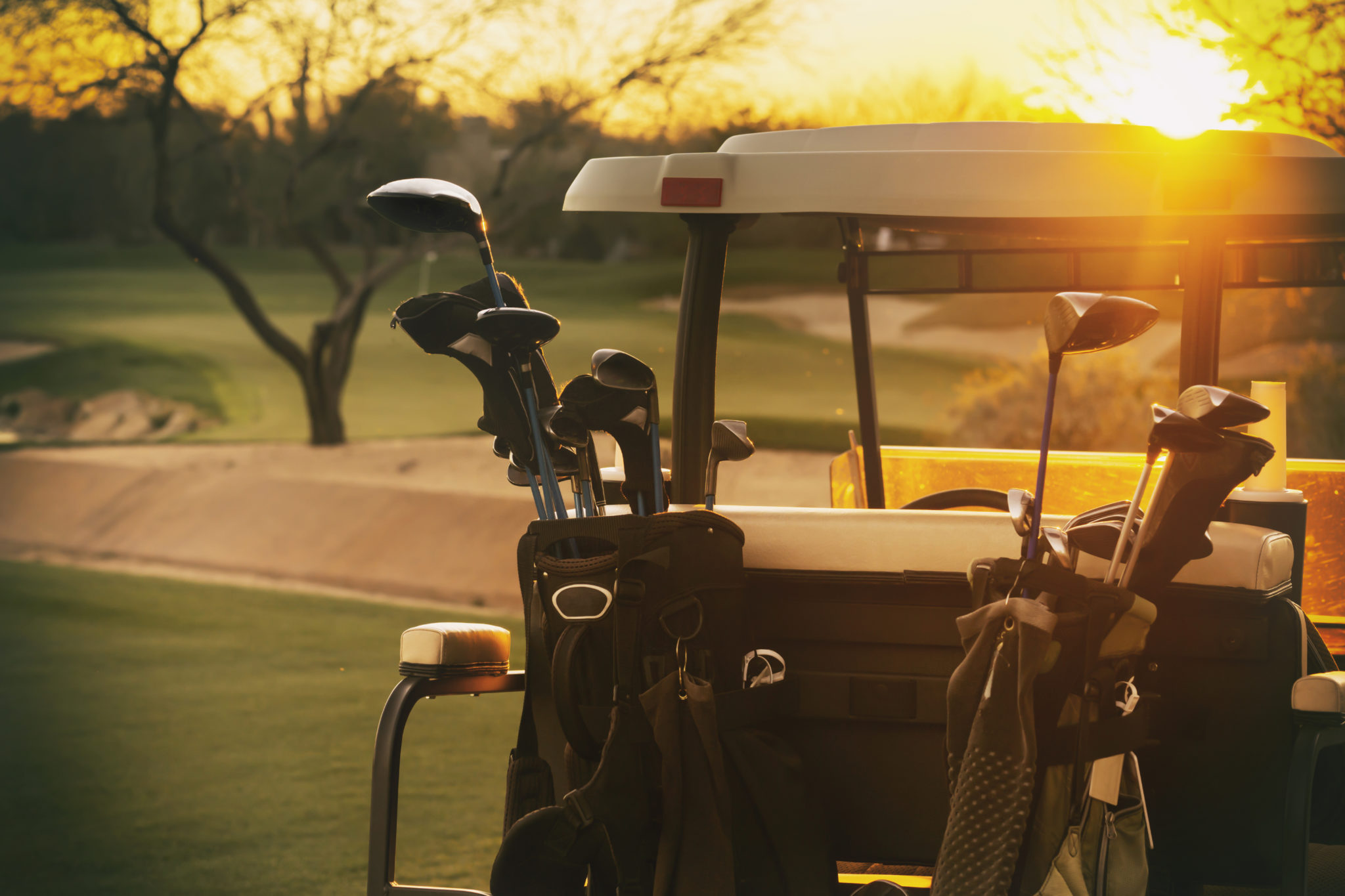 a golf cart with a bag of golf clubs sits empty on the golf course as the sun is rising