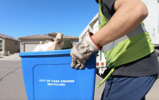 blue recycle bin being picked up and throw into back of garbage truck